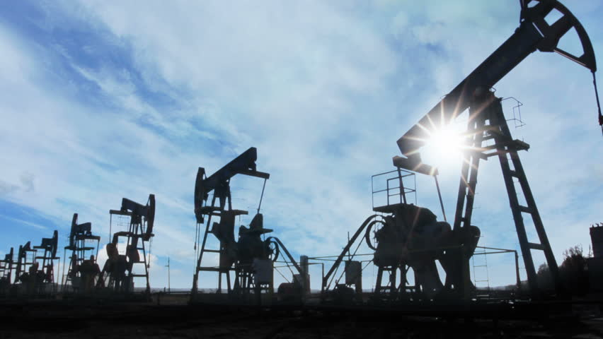 working oil pumps silhouette against timelapse clouds - HD stock footage clip