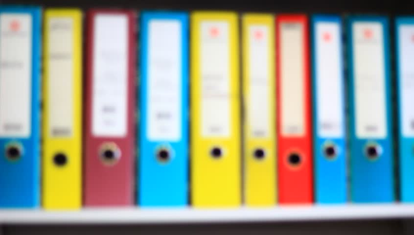 Colorful file folders in the office. Blurred clip, while camera pans. - HD stock video clip
