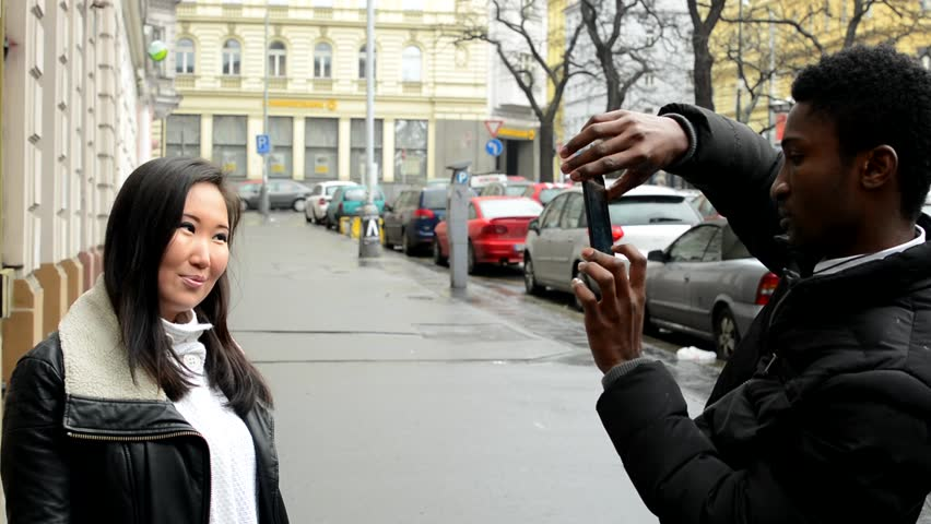 Happy couple takes photo - black man and asian woman - urban street - city - HD stock video clip