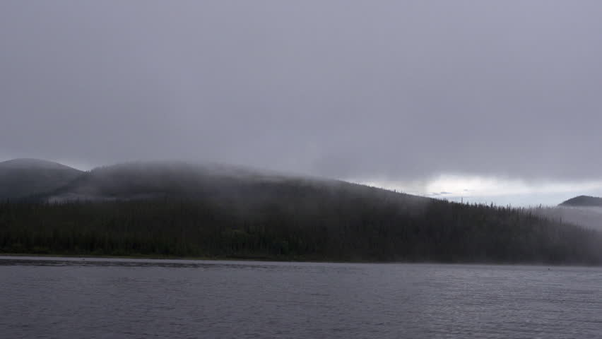 A front view from boat traveling across a mountain lake in the mist | Shutterstock HD Video #8974222