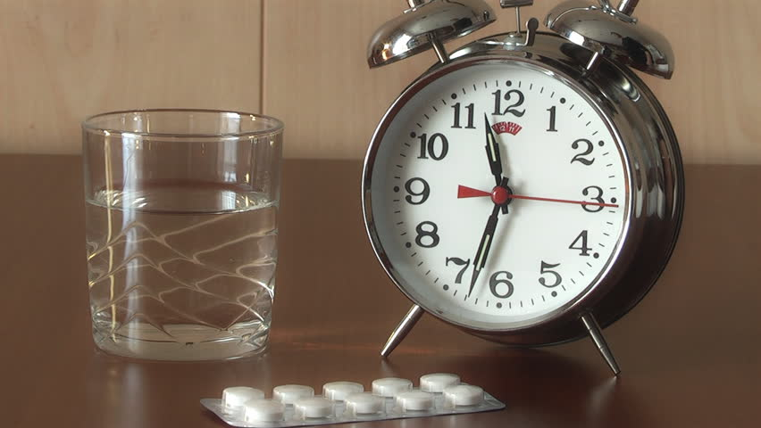 Alarm Clock and Pills on the table, medicine and curing theme, taking pills on schedule