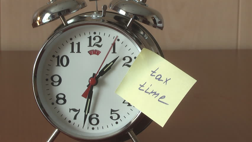 """An alarm clock and a yellow note with this text: """"tax time """""""