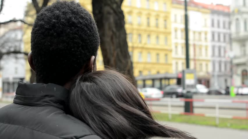 Couple looks to the urban street in the city - black man and asian woman - cars and passing tram