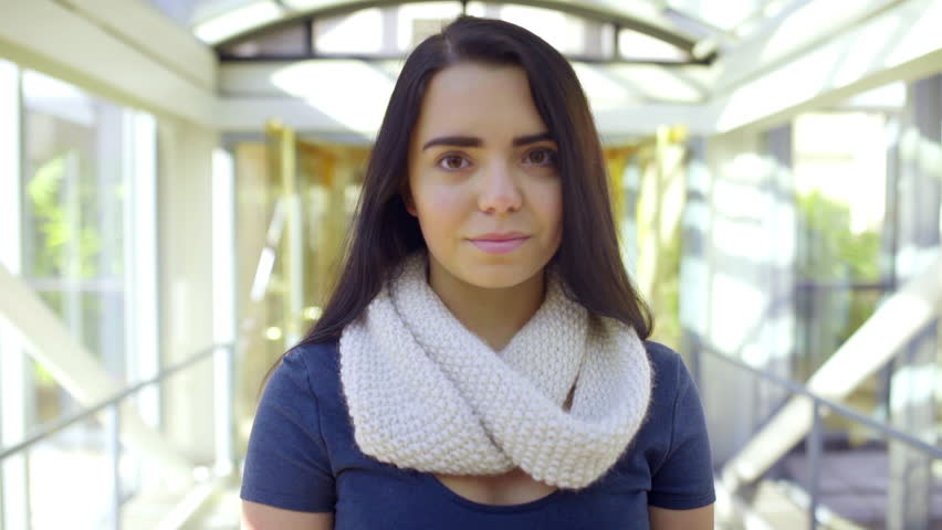 Mixed Race Teen Looks Down And Then Up At Camera With A Smile (Inside A Skybridge)