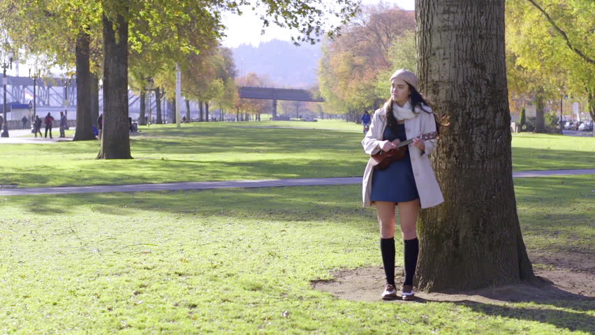 Mixed Race Young Woman Plays Her Ukulele In A City Park In Autumn