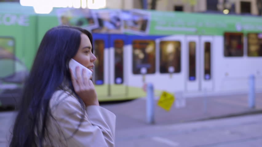 Mixed Race Young Woman Talks On Phone, And Walks Toward Train