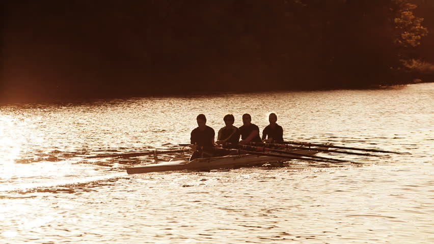 Women rowers in training on the water at sunrise, seen in silhouette