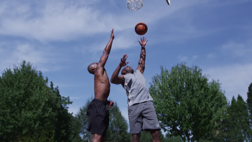 One on one street basketball; player makes layup - 4K stock video clip