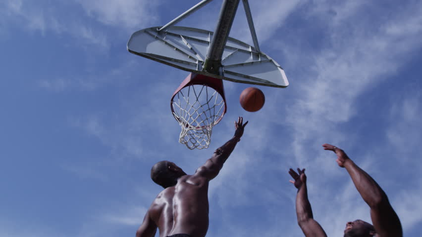 One on one street basketball; low angle looking up at player shooting - 4K stock footage clip