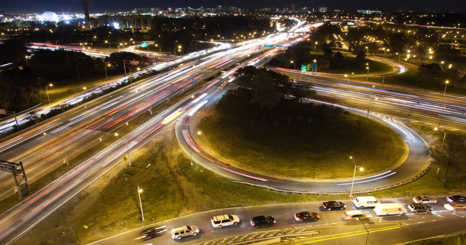 Timelapse New York City of traffic on the Grand Central Parkway in Flushing Queens with the World's fair Unisphere and Tower and  Arthur Ashe Stadium in shot at night. Verrazano Bridge in distance.