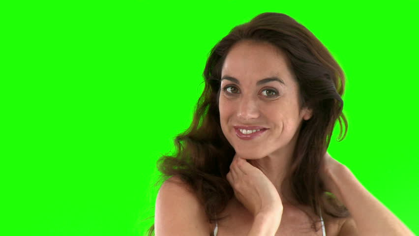 Smiling hispanic woman smiling at the camera against a green background  - HD stock footage clip