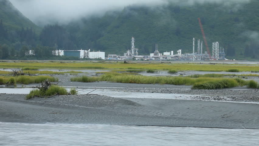 Tidal river with an oil refinery in the distance. Forest and mountain at Valdez, Alaska, the site of an environmental oil spill. End of the Alaskan oil pipeline.  Fog shrouds the mountain peaks.  - HD stock video clip