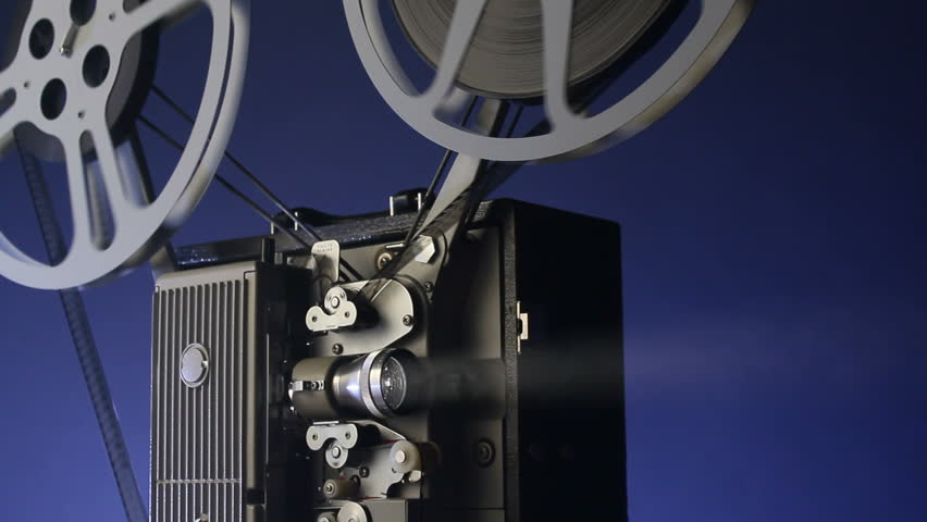 A motion picture movie projector sends a beam of light into the dark - HD stock video clip