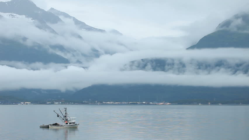 Fishing trawler anchored in fjord bay with Valdez, Alaska, mountains and beautiful fog and clouds in the background. Early morning calm. - HD stock footage clip