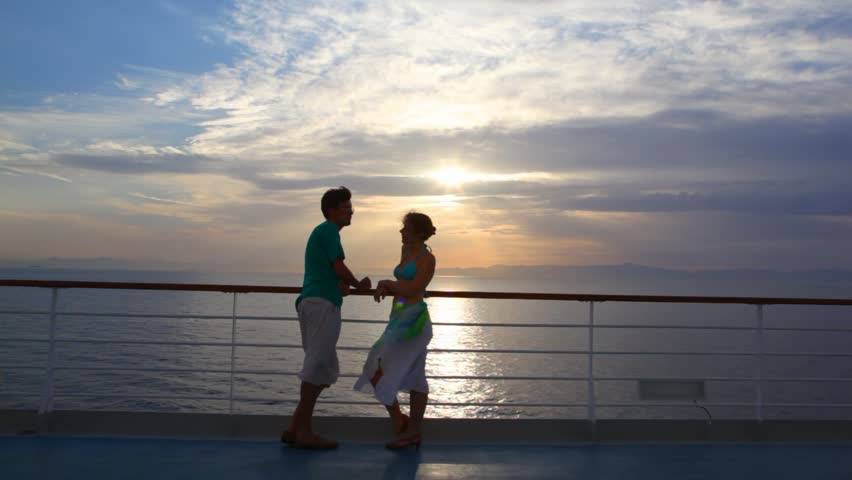 couple having joined hands stands on ship moving in sea during sunset - HD stock video clip