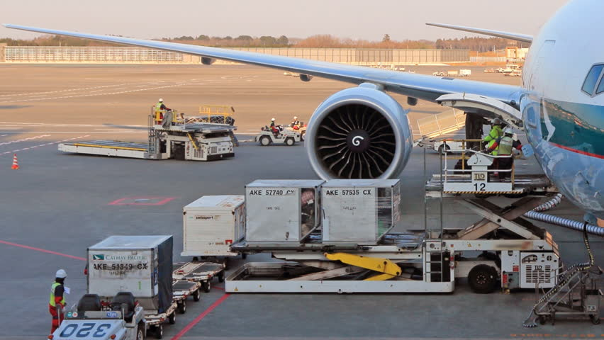 NARITA, JAPAN - DECEMBER 31, 2015: Baggage handlers ready to load and unload cargo at NARITA INTERNATIONAL AIRPORT, JAPAN.