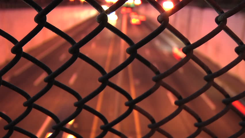 Time Lapse of traffic through a fence on a bridge  - HD stock footage clip