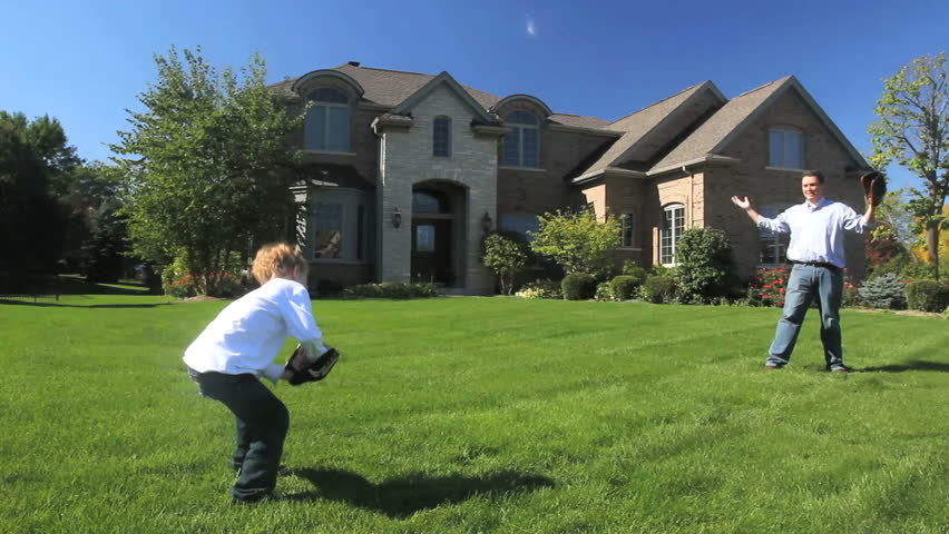 A father and young son play catch in front of their luxury home