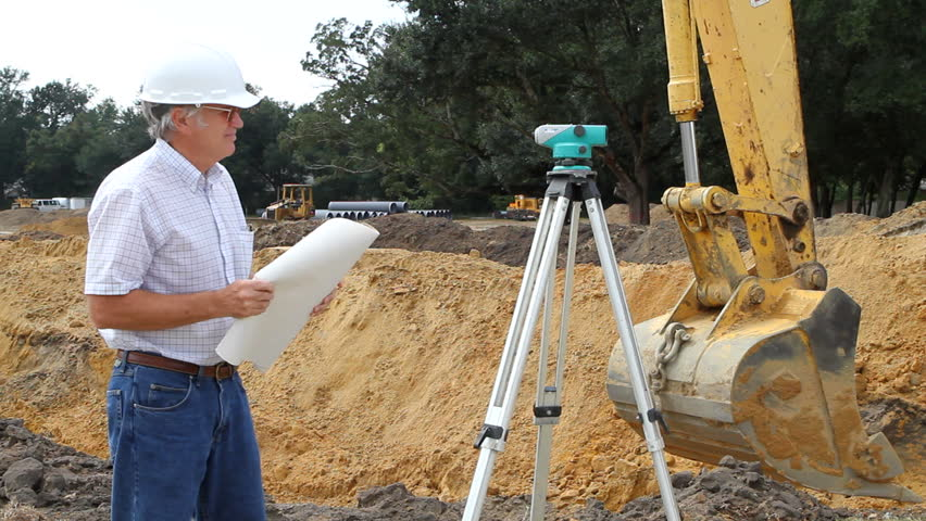 Civil engineer reads architectural blueprints and inspects the work at a construction site. - HD stock video clip