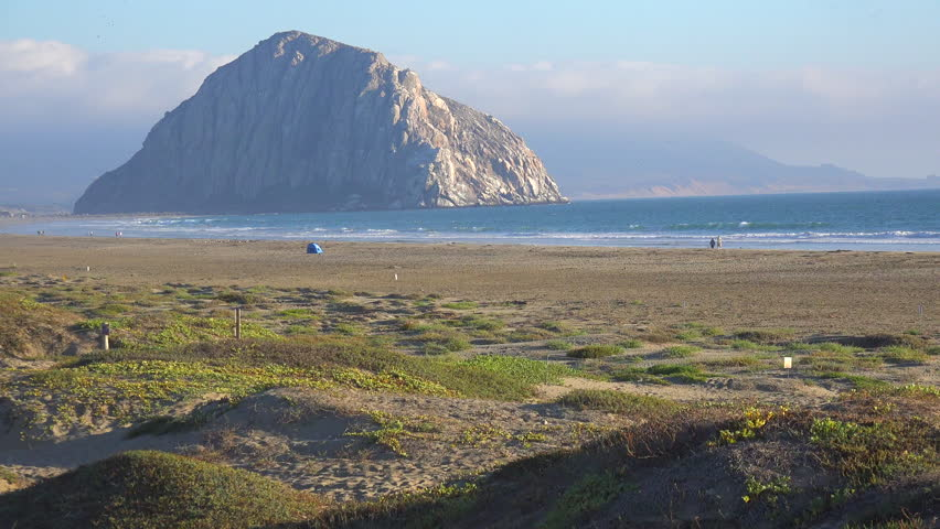 MORRO BAY, CALIFORNIA - CIRCA 2014 - The beautiful rock at Morro Bay California in golden sunset light. - 4K stock video clip