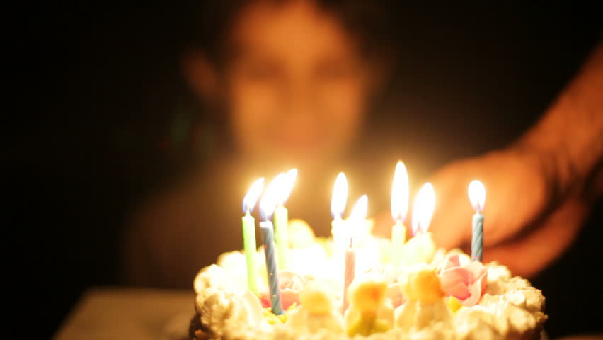 Boy claps and blows out candles on birthday cake.  - HD stock video clip