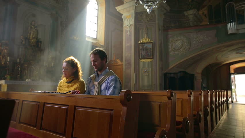 SENTJUR, SLOVENIA - OCTOBER 2014: Couple seating in the catholic church . On this footage we can see the tourist couple seating in the local catholic church and praying to a bright future. - HD stock footage clip