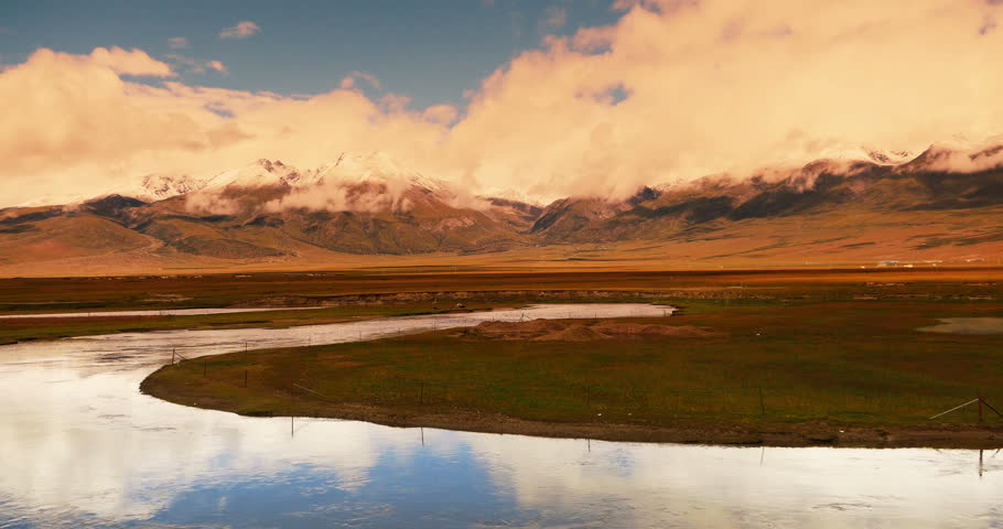 4k time lapse of white puffy clouds mass rolling over Tibet mountaintop & valley in sunset,river flowing through the prairie,cattle & sheep flocks,Danggula Mountains in xizang Plateau.