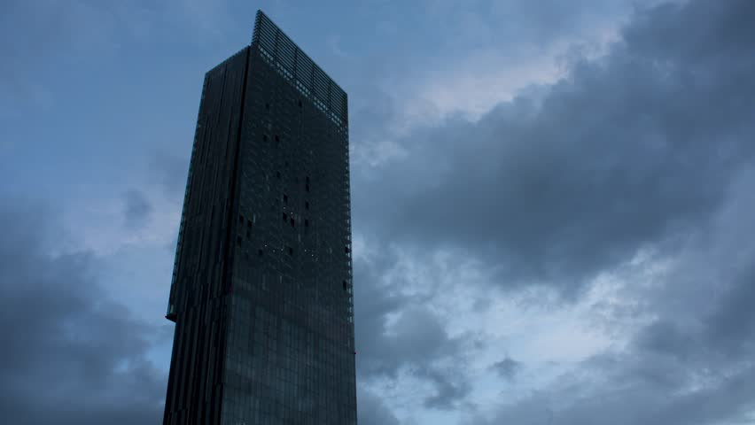 4K time lapse of Hilton Hotel in Manchester with clouds passing at nightfall
