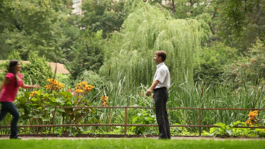 Happy couple embracing and whirling around in beautiful garden - HD stock footage clip
