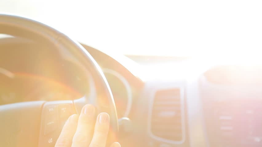 Woman hands holding car wheel while sun shining in windglass