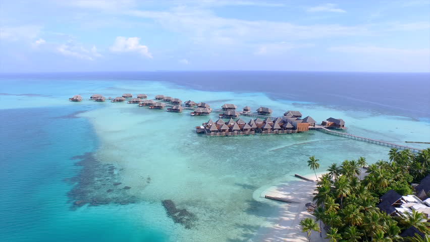 AERIAL: Luxurious over-water villas on tropical island resort