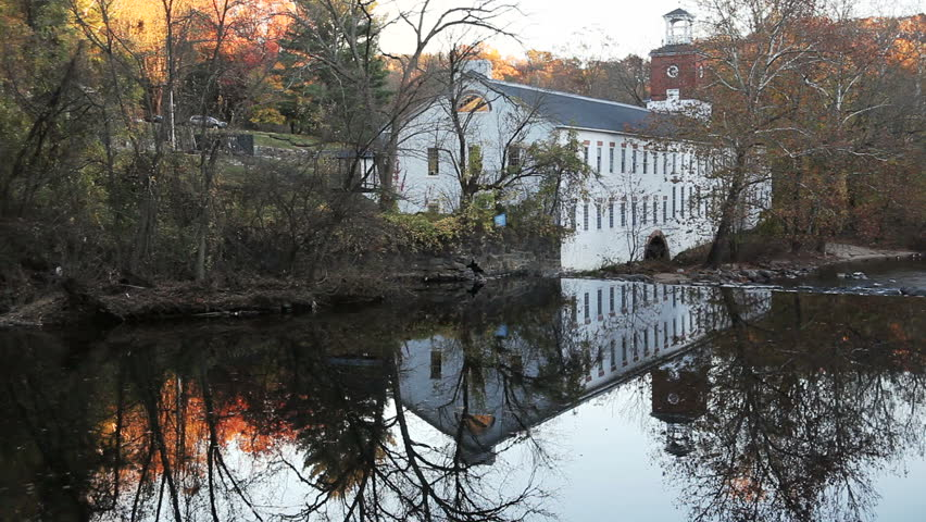 A historical building located along the Brandywine River, with it's reflection visible in the water. - HD stock video clip