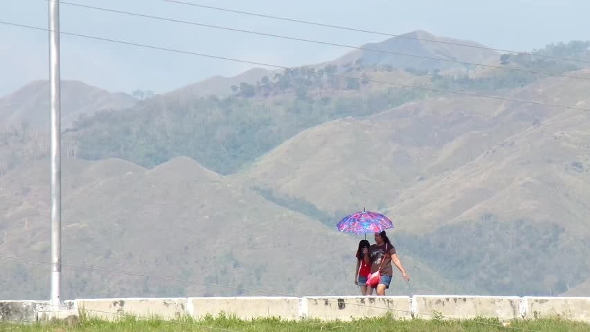SANTO DOMINGO, ALFONSO LISTA, IFUGAO - APRIL 3, 2015: two women with umbrella walking on mountain high way