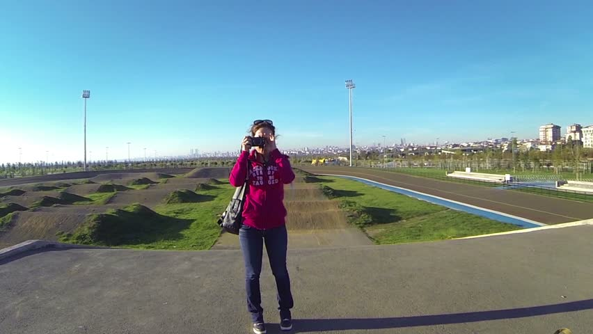 Young girl filming the drone with a mirrorless camera