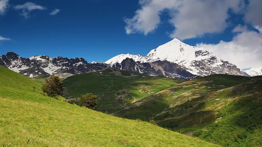 Great view of the green meadows with blue sky at the foot of Mt. Tetnuldi. Upper Svaneti, Georgia, Europe. The main Caucasian ridge. Beauty world. HD video (High Definition)