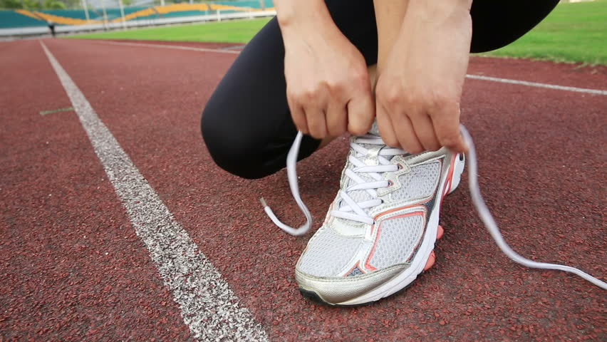 young woman runner tying shoelaces on track