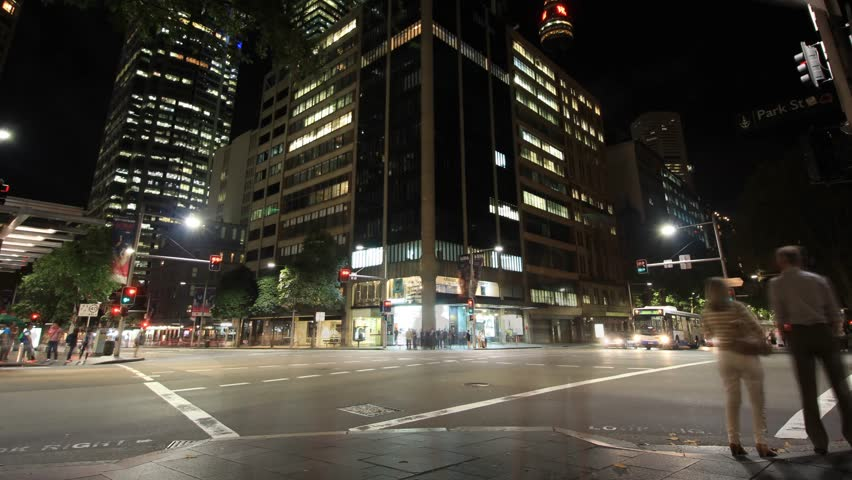 4K establishing shot footage of city street night traffic pedestrian time lapse with slow shutter to get the blurred motion effect. This was shot on the streets of Sydney Australia.