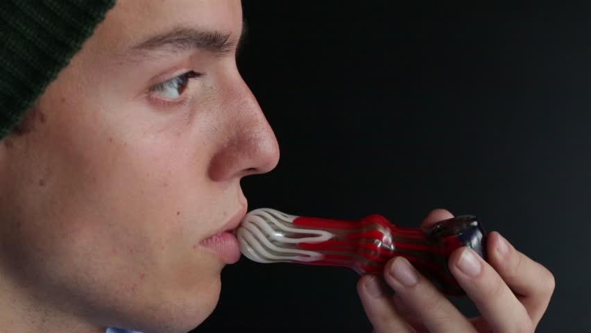 Young Man Smokes Medical Marijuana with Pipe Close Up