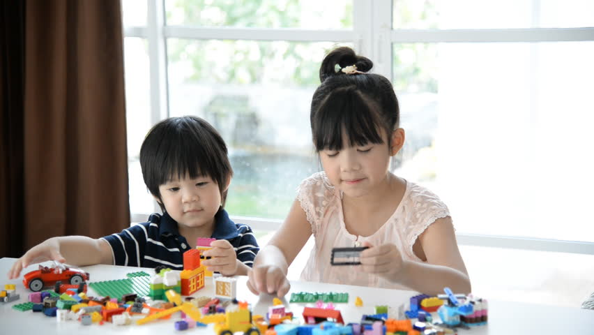 Little asian children  playing with colorful construction blocks on white table - HD stock footage clip