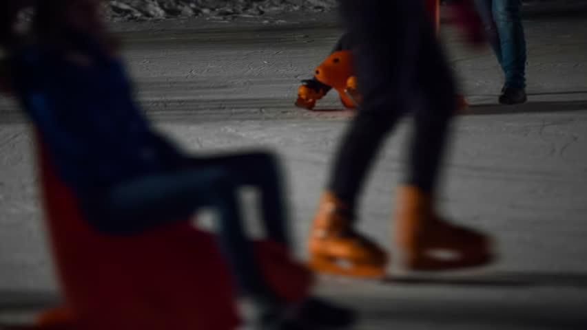 Skating on special sleds. Close up on kid sit on plastic sled with parent pushing from behind enjoying skating at night. - HD stock video clip