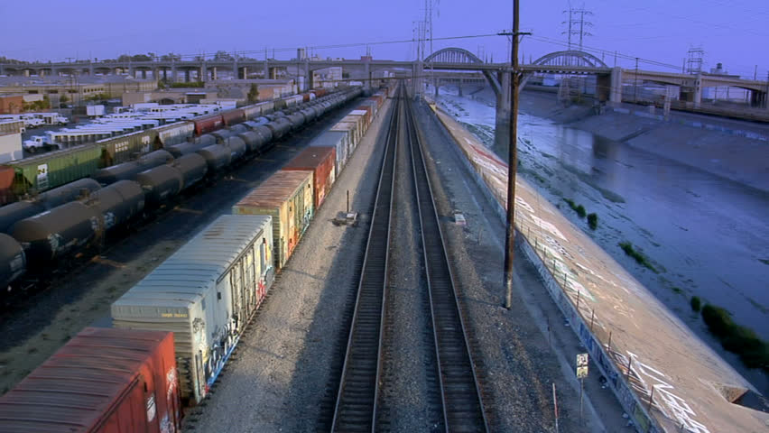 A train runs through a seedy train yard next to the Los Angeles river.  Very