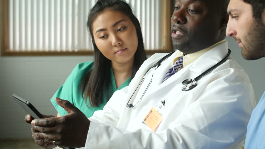 Diverse medical team consulting with tablet