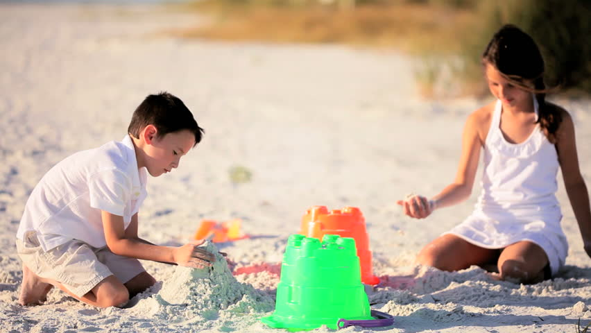 Happy healthy children having fun playing on the beach making sand castles - HD stock video clip