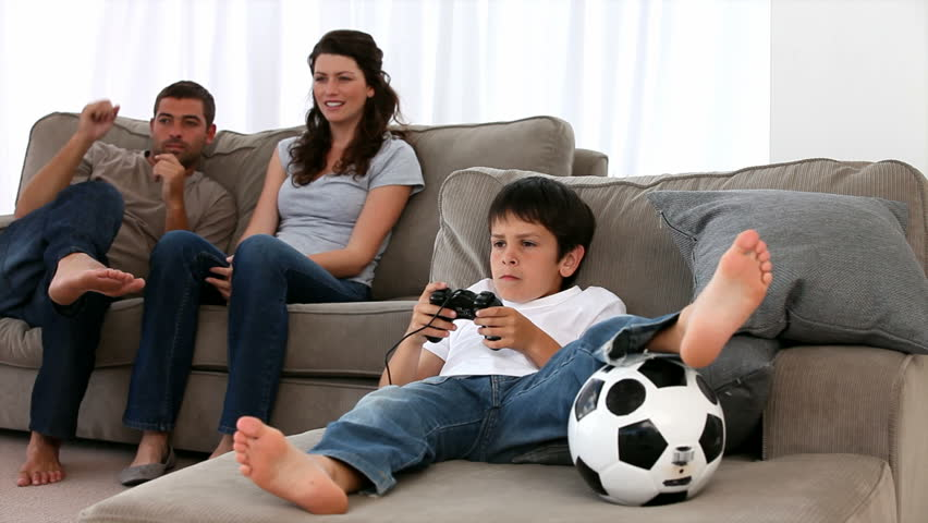 Parents Watching Their Children Play Video Games At Home  : 1 from shutterstock.com size 852 x 480 jpeg 45kB