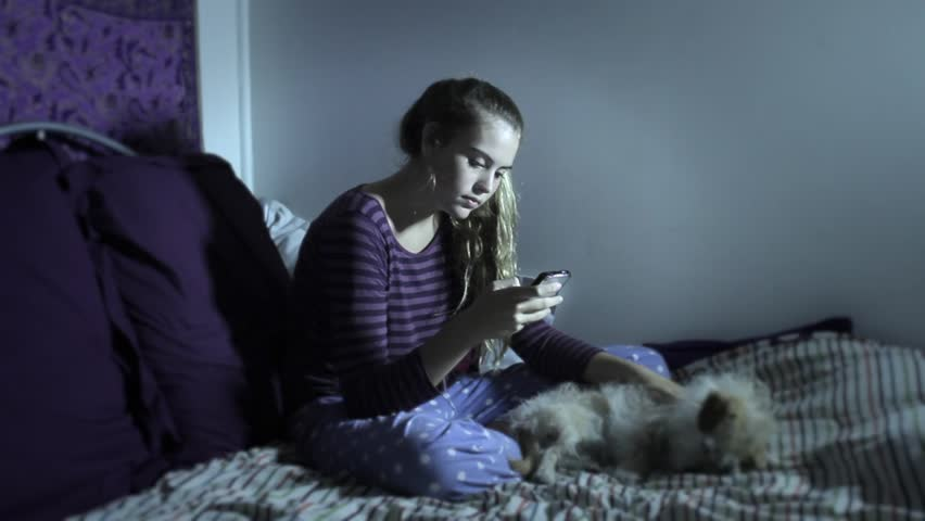 Young Depressed Teenage Girl On Bed Interacting With ...