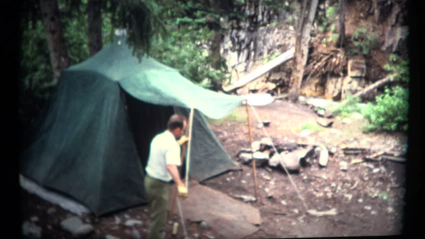 BOULDER, COLORADO. USA - JUNE 1967:  Man Setting Up a Old Camping Tent. Camping out means setting up a great tent for the trip.