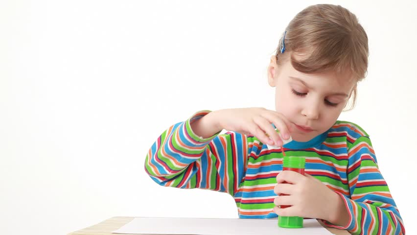 little girl sitting and blowing soap bubbles on white background - HD stock footage clip