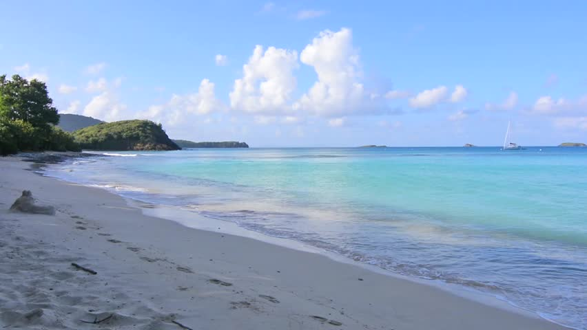 Calm turquoise shallow waters of Caribbean Sea lap on white sand beach on Playa Carlos Rosario while a sailboat lies anchored off shore of Isla Culebra with natural ambient sounds of the beach - HD stock video clip