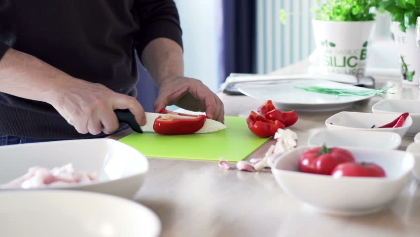 Man preparing pepper and removing seeds in kitchen at home