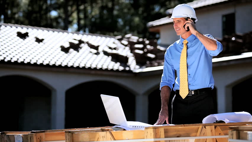 Male architect working on new home plans on site talking on his cell phone - HD stock video clip